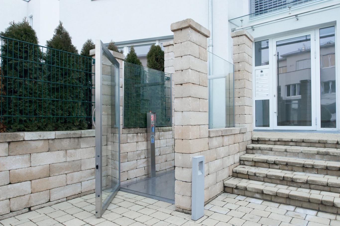 Die Plattform-Hebebühne GBH 50 als Rollstuhllift vor einem Mietshaus installiert
